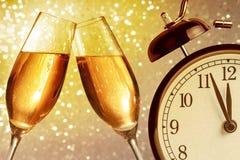 Champagne-fluiten met gouden bellen op gouden lichte bokehachtergrond met uitstekende wekker Royalty-vrije Stock Foto's