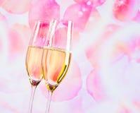 Champagne-fluiten met gouden bellen op onduidelijk beeldbloemblaadjes van rozenachtergrond Stock Foto's