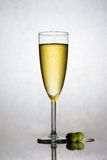 Champagne in a flute. A fresh flute filled with sparkling champagne and two olive Stock Images