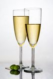Champagne in a flute. Two fresh flute filled with sparkling champagne and two olive Royalty Free Stock Photography