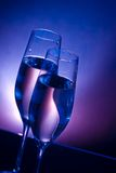 Champagne flutes on bar table on dark blue and violet light background. With space for text Stock Photography