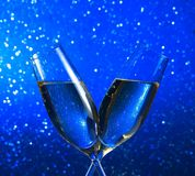 Champagne flutes on blue light bokeh background Royalty Free Stock Photography