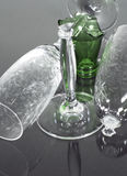 Champagne flutes and bottle. A broken champagne flute next to a solid one, with a broken bottle top in the middle. isolated on a black reflective background Stock Photography