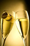 Champagne flutes and bottle cap on gold background Royalty Free Stock Photos
