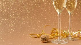 Champagne flutes on golden holiday background. Champagne flutes and bottle cork with 2019 numbers at golden holiday background with glitters and tinsel Stock Photos