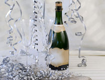 Champagne Flutes Decorated. Two champagne flutes waiting to be filled, decorated with silver ribbons, surrounded by silver streamers, pearls and beaded royalty free stock photo