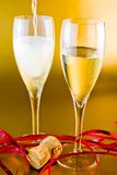 Champagne flutes and decoration on gold background Royalty Free Stock Photography