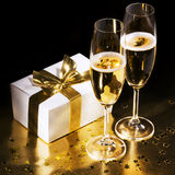 Champagne flutes with gift. Champagne flutes with white giftbox stock photography