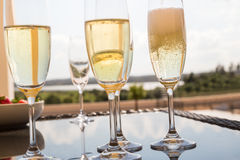 Champagne flutes on a glass table outside Stock Images