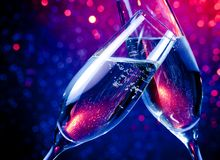 Champagne flutes with gold bubbles on blue tint light bokeh background Royalty Free Stock Image