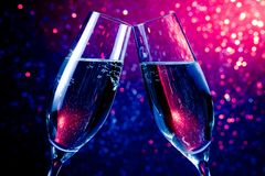 Champagne flutes with gold bubbles on blue tint light bokeh background Royalty Free Stock Images