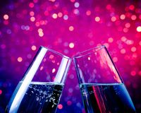 Champagne flutes with gold bubbles on blue tint light bokeh background. Pair of champagne flutes with gold bubbles make cheers on blue tint light bokeh Royalty Free Stock Photos