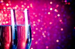 Champagne flutes with gold bubbles on blue and violet tint light bokeh background. Pair of champagne flutes with gold bubbles on blue and violet tint light bokeh Royalty Free Stock Photos