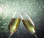 Champagne flutes with gold bubbles on green light bokeh background Royalty Free Stock Photography