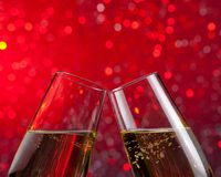 Champagne flutes with gold bubbles on red light bokeh background Royalty Free Stock Images