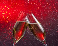 Champagne flutes with gold bubbles on red and violet light bokeh background Royalty Free Stock Image