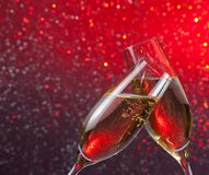 Champagne flutes with gold bubbles on red and violet light bokeh background Stock Photos