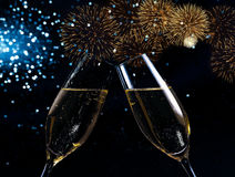 Champagne flutes with golden bubbles on blue light bokeh and fireworks sparkle background Stock Photos