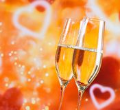 Champagne flutes with golden bubbles on blur decorative hearts background Stock Photo