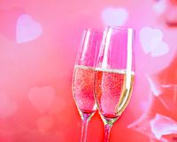 Champagne flutes with golden bubbles on blur decorative hearts background Stock Image