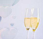 Champagne flutes with golden bubbles on blur decorative hearts background Stock Images
