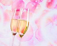 Champagne flutes with golden bubbles on blur petals of roses background Stock Photos