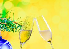 Champagne flutes with golden bubbles on christmas decoration yellow bokeh background Stock Images