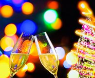 Champagne flutes with golden bubbles on christmas lights bokeh decoration background Stock Images
