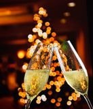 Champagne flutes with golden bubbles on christmas lights decoration background. Champagne flutes with golden bubbles make cheers on christmas lights decoration Royalty Free Stock Images