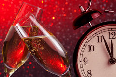 Champagne flutes with golden bubbles on christmas red light bokeh background with vintage alarm clock Royalty Free Stock Images