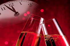 Champagne flutes with golden bubbles on christmas red light bokeh background with vintage alarm clock Stock Image