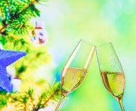 Champagne flutes with golden bubbles on christmas tree decoration background Stock Photography