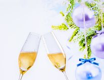 Champagne flutes with golden bubbles on christmas tree decoration background Royalty Free Stock Photos