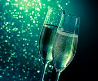 Champagne flutes with golden bubbles on dark green light bokeh background. With space for text Royalty Free Stock Photos