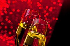 Champagne flutes with golden bubbles on dark red light bokeh background Royalty Free Stock Images