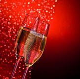 Champagne flutes with golden bubbles on dark red light bokeh background. With space for text Royalty Free Stock Images