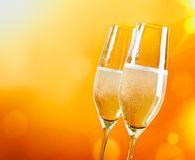 Champagne flutes with golden bubbles on golden light background Royalty Free Stock Image