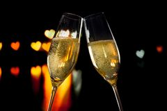 Champagne flutes with golden bubbles on hearts bokeh background Royalty Free Stock Photo