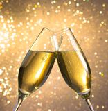 Champagne flutes with golden bubbles on light bokeh background Royalty Free Stock Photo