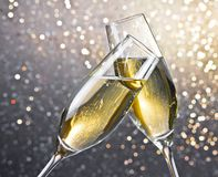 Champagne flutes with golden bubbles on light bokeh background Stock Images