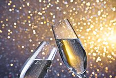 Champagne flutes with golden bubbles on light bokeh background. Champagne flutes with golden bubbles make cheers on light bokeh background with space for text Stock Photo