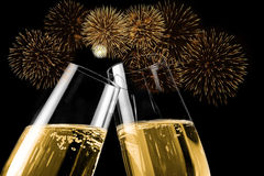 Champagne flutes with golden bubbles make cheers with fireworks sparkle and black background. Happy new year concept royalty free stock image