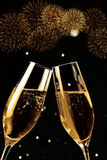 Champagne flutes with golden bubbles make cheers with fireworks sparkle and black background Stock Photography