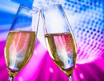 Champagne flutes with golden bubbles make cheers on sparkling blue and violet disco ball background Royalty Free Stock Image