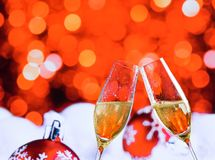 Champagne flutes with golden bubbles on red christmas lights bokeh and balls decoration background. Champagne flutes with golden bubbles make cheers on red Royalty Free Stock Photo