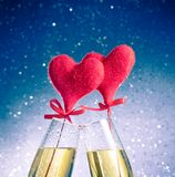 Champagne flutes with golden bubbles and red velvet hearts make cheers on blue bokeh background Stock Photos