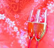 Champagne flutes with golden bubbles on red vintage background Stock Photos