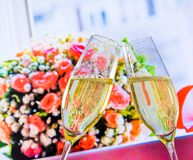 Champagne flutes with golden bubbles on wedding flowers background Royalty Free Stock Images