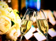 Champagne flutes with golden bubbles on wedding flowers background Royalty Free Stock Photo