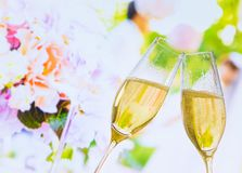 Champagne flutes with golden bubbles on wedding flowers background Royalty Free Stock Image